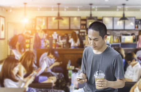don't care: Asian man with beautiful smile reading good news on mobile phone during rest in blurred coffee shop background, happy man watching his photo on cell telephone while relaxing in cafe during free time Stock Photo