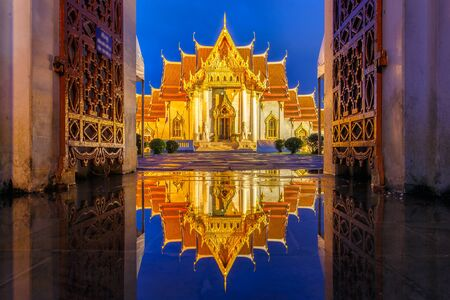 be soggy: Wat Benchamabophit in Bangkok at twilight time with reflection on the water after hard raining, Bangkok, Thailand Stock Photo