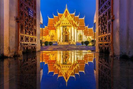 be soggy: Wat Benchamabophit in Bangkok at twilight time with reflection on the water after hard raining, Bangkok, Thailand Stock Photo