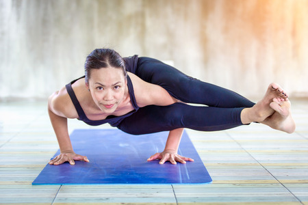 Asian trainee strong woman practicing difficult yoga pose in a concrete background Standard-Bild