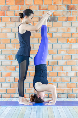 legging: Asians female trainer helping young woman doing yoga.