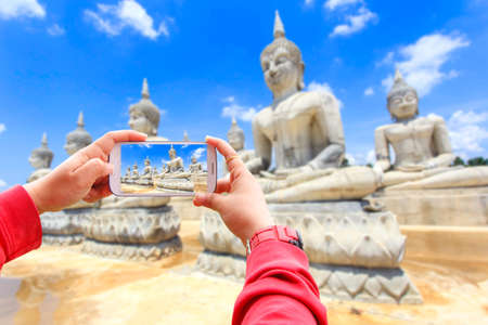 Smartphone photographing buddha statue and blue sky, Nakhon Si Thammarat Province, Thailand