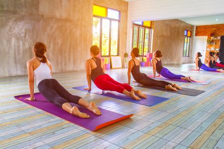 clase media: La aptitud del grupo hembra asiática que hace el calentamiento pose de yoga en la fila en la clase de yoga. enfoque selectivo Foto de archivo
