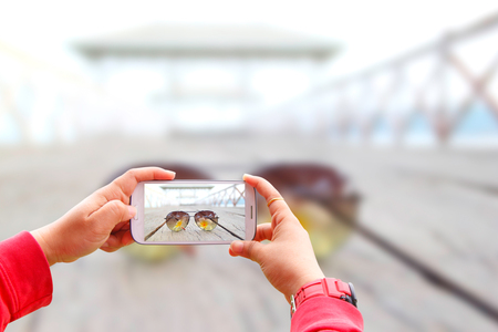 generic location: Smartphone photographing sunglass on the bridge Stock Photo