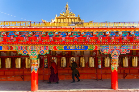 buddhism prayer belief: Buddhist monk walking touch a prayer wheels around the sanctuary at Larung gar (Buddhist Academy) in Sichuan, China. This is the public place Stock Photo