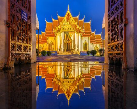 soggy: Wat Benchamabophit in Bangkok at twilight time with reflection on the water after hard raining, Bangkok, Thailand Editorial