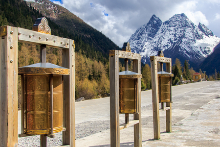 four peaks wilderness: Maidens Mountain Scenic Area is an unspoiled wilderness park located in western china and Qiang Autonomous Prefecture at Prayer wheels foreground , Sichuan Province, China. selective focus