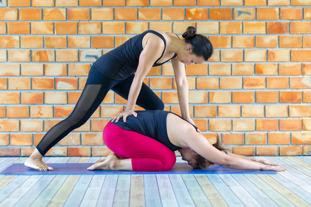 Asians female trainer helping young woman doing yoga.