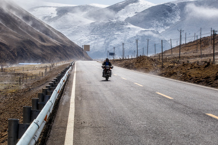 Biker motorcycle on the road beautiful winter in Tibet under snow mountain, Sichuan, China