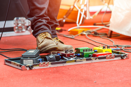 Feet of guitar player on a stage with set of distortion effect pedals. Selective focus