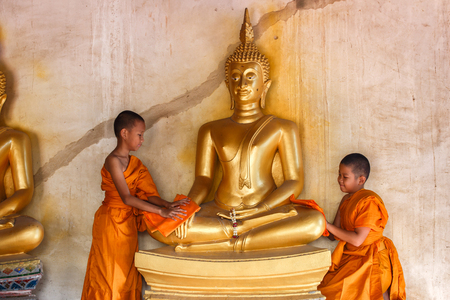 scrubbing: Two young novices monk scrubbing buddha statue at temple in thailand Stock Photo