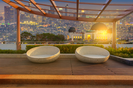 Relax corner on condominium rooftop garden with chairs on Landscape of the Griffith Observatory and Los Angeles city skyline at twilight time background, Landmark concept
