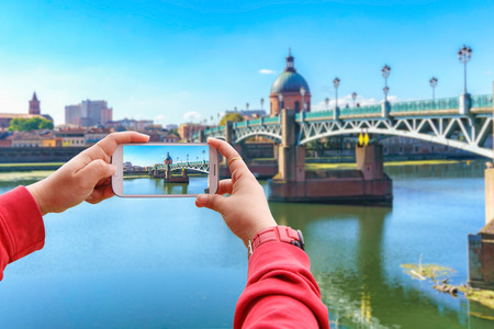 Smartphone photographing the Saint-Pierre bridge passes over the Garonne and it was completely rebuilt in 1987 in Toulouse, Toulouse, France