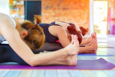 clase media: La aptitud del grupo hembra asiática que hace namaste yoga plantean en la fila en la clase de yoga. enfoque selectivo