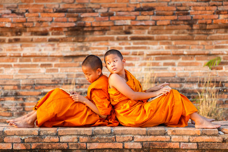 Two novice reading and studying blackboard with funny in old temple at sunset time, Ayutthaya Province, Thailand Stock Photo