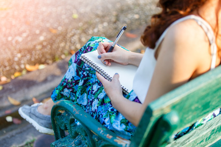 Beautiful asian women with pen writing notebook and sitting on a wooden bench and in a park