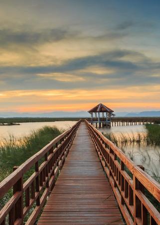 Wooden Bridge in lotus lake on sunset time at Khao Sam Roi Yot National Park, Thailand Stock Photo