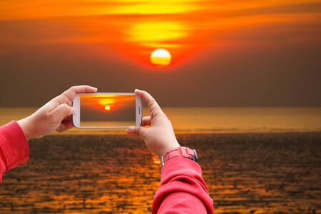 Smartphone Concept, Smartphone photographing big sunset on the beach, Similan Island, Koh Ta Chai, Andaman Sea, Thailand Stock Photo