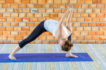 Asian trainee strong woman practicing difficult yoga pose in a concrete background Stockfoto