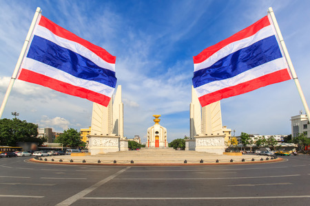 Democracy monument with blue sky and thai flag foreground in sunshine day, Bangkok, Thailand
