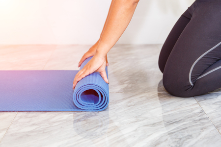 unfolding: Close-up of attractive young woman folding blue yoga or fitness mat after working out at home in living room. Healthy life, keep fit concepts.