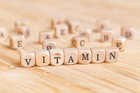 Close up vitamin word made from wooden letters on the table and A B C D E on the table background, Health concept Stock Photo