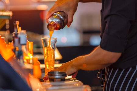 Close up process of preparing a cocktail bartenders from passion fruits
