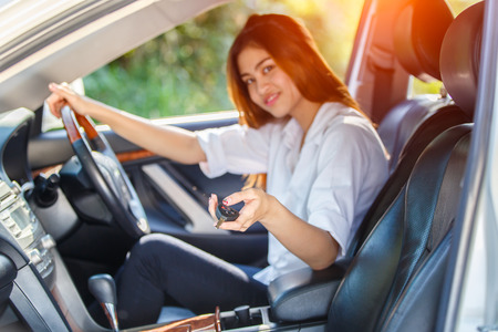 open autocar auto:  Young asian woman driver driving a car on the road in countryside and hand presses on the remote control car alarm systems  Stock Photo