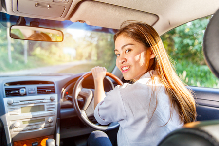 Young asian woman driver driving a car on the road in countryside