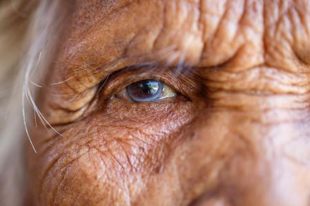 Alter, Vision und altes Leutekonzept - nah oben vom älteren asiatischen Frauengesicht und -auge Standard-Bild - 74476263