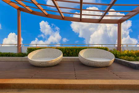 velours: Relax corner on condominium rooftop garden with chairs on blue sky background Stock Photo