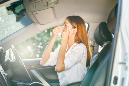 Woman watching her makeup in the mirror while driving a car and try to cool himself on the hot sunny day
