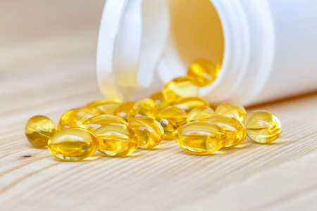 vitamine: Fish oil capsules with omega 3 and vitamin D on spoon wood with wooden background, healthy diet concept