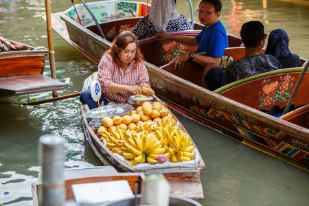 RATCHABURI, THAILAND - MARCH 20 : Local vendors selling goods at Damnoen Saduak Floating Market near Bangkok in Thailand on March 20, 2016. Damnoen Saduak is a very popular tourist attraction.