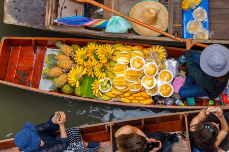 Traveler enjoying and take a photo with smartphone on long trail boat at Damnoen Saduak floating market in Ratchaburi near Bangkok, Thailand Фото со стока