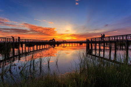 Wooden Bridge in lotus lake on sunset time at Khao Sam Roi Yot National Park, Thailand Stock Photo