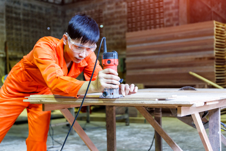 Asian young man carpenter working with grinder on wooden factory background.