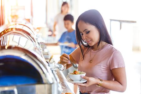 아름 다운 타이 아시아 여자 손을 잡고 mush 또는 삶은 쌀 돼지 고기 레스토랑에서 뷔페에서 태국 스타일에 대 한 아침 식사 호텔에서 아침 식사 뷔페 셀 스톡 콘텐츠