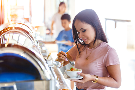 Portrait of beautiful thai asian women hand holding mush or boiled rice pork for thai style at buffet in restaurant, Breakfast buffet self service in morning at hotel.