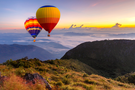 Colorful hot-air balloons flying over the Doi Luang Chiang Dao with sunrise and morning mist at Chiang mai, Thailand. Stock Photo