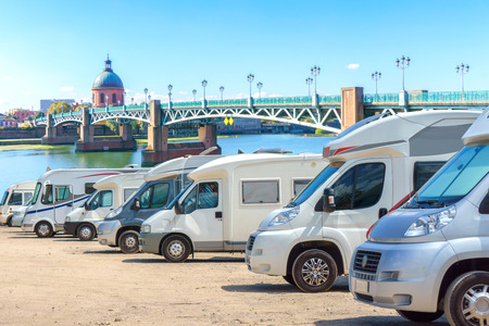motorcoach: Close up motorhomes parked in a row on background The Saint-Pierre bridge passes over the Garonne river in Toulouse, France Stock Photo