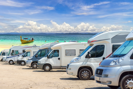 Close up motorhomes parked in a row on white sand beach and blue sky background. Stock Photo