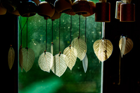 Chimes hanging in the window, Decorative bells hang on the window behind with bokeh background, The traditional wind bell fluttering in tropical wind in Thai house.