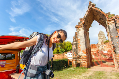 Young asian female traveler with backpack traveling with standing on taxi or Tuk Tuk and happy fun with old temple (Wat Mahathat) background, Ayutthaya Province, Thailand