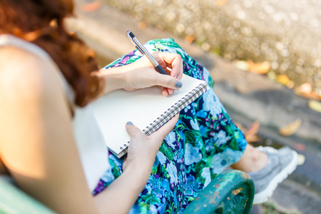 Close up left hand asian women with pen writing notebook and sitting on a wooden bench and a park.