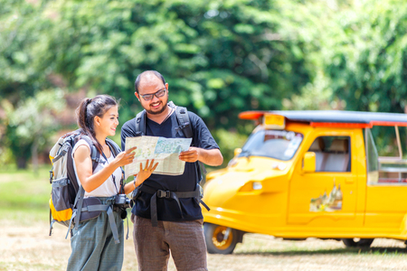 Asians love couple enjoying look at map travel with yellow taxi or tuk tuk touring background, Ayutthaya Province, Thailand