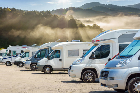 Close up motorhomes parked in a row with fog in the morning background, Chiang Mai Province, Thailand