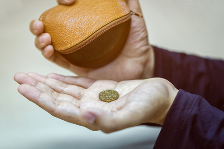 Hands holding one dollar coin and small money pouch.