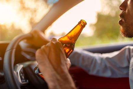 술 취한 아시아 젊은이 일몰 배경 가진 맥주 한 병 차를 운전, 위험한 운전 개념 스톡 콘텐츠