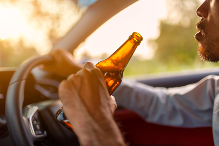 Drunk asian young man drives a car with a bottle of beer with sunset background, Dangerous driving concept